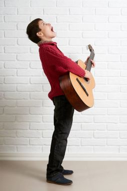 Boy posing with acoustic guitar