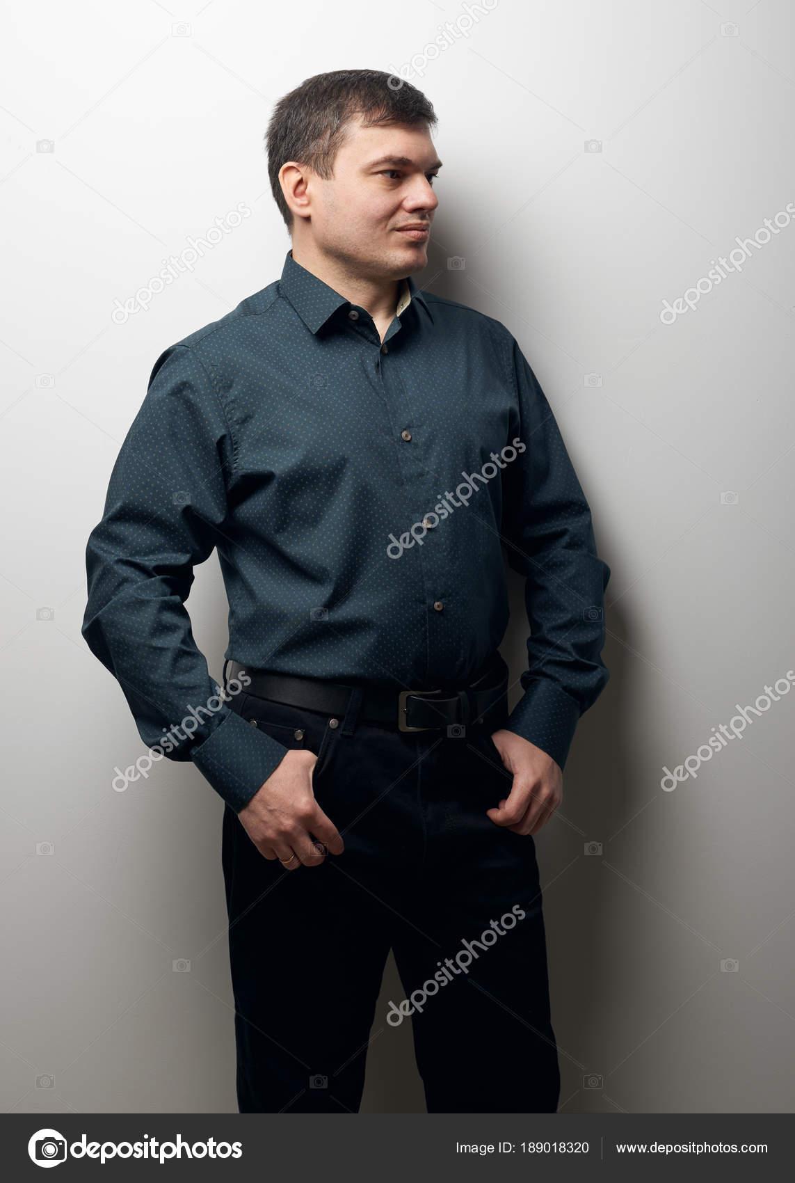 man kijkt opzij, gekleed in donkere shirt en zwarte broek
