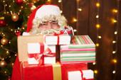 Fotografie Santa Claus pózování s mnoha dárky, sedí uvnitř v blízkosti zdobené vánoční strom se světly - Veselé Vánoce a šťastné svátky!
