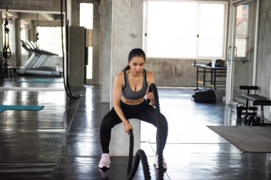 Asian woman battle rope exercise in gym