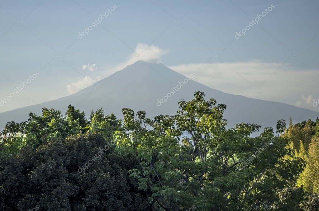 Morning view of the beautiful Popocatepetl Mountain at Puebla, Mexico. View of Popocatepetl mountain with trees and blue sky