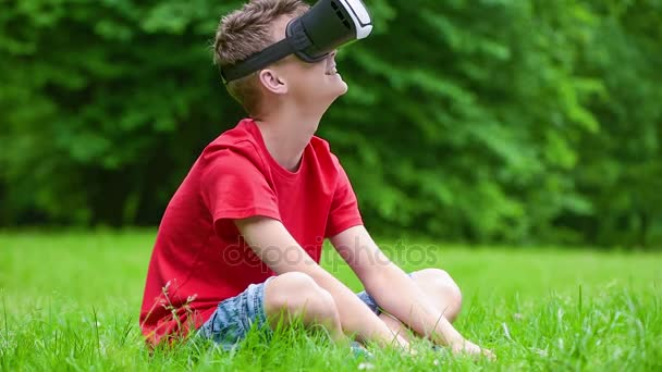 Teen boy with VR glasses in park