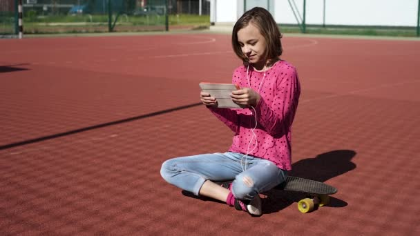 Teen girl with headphones and tablet