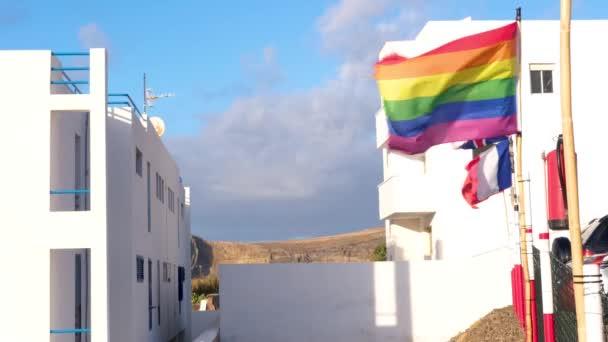 Vlnění Gay Pride Rainbow Flag vedle vlajek evropských států na Gran Canaria ve Španělsku, symbol komunity Lgbt na hrdosti. Bílé domy a hory na pozadí. Lidská práva, rovnost.