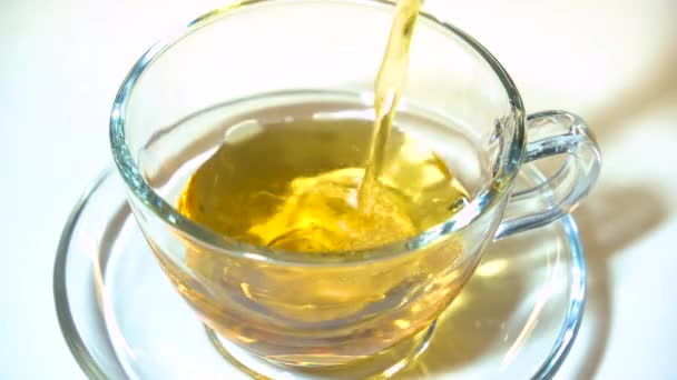 Pouring aromating black tea from teapot into a matching transparent glass tea cup on white background closeup.