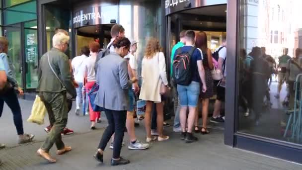 A crowd of Multiethnic people enters a shopping mall, business center or airport through glass doors. City summer day, city residents and tourists. Gallery center. St.Petersburg 18aug2019