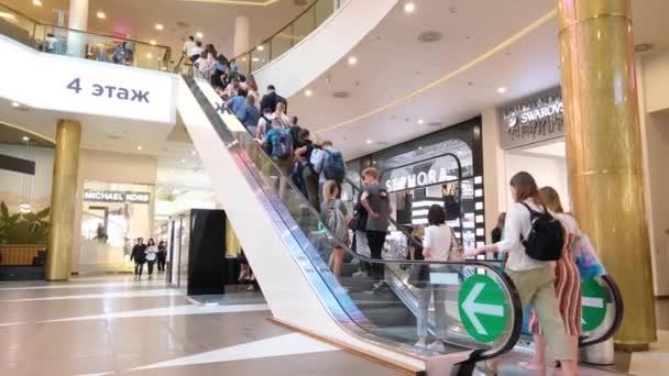 Mozgásban lévő emberek mozgólépcsőn a modern bevásárlóközpontban. Nyári nap. Galéria központ. Szentpétervár Oroszország 18aug2019