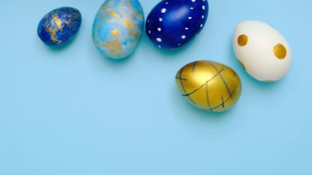 Velikonoční vajíčka se kutálí a srazí se na modrý stůl. Vejce trendy barevné klasické modré, bílé a zlaté. Veselé Velikonoce. Minimální styl. Horní pohled