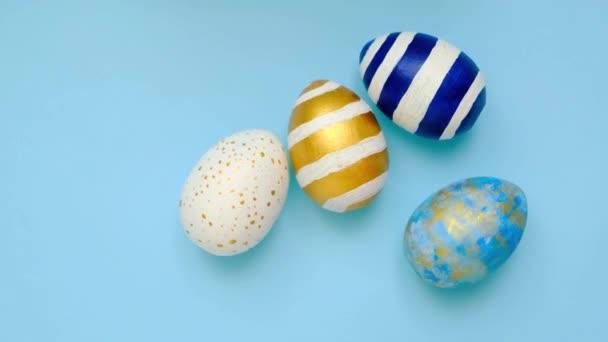 A húsvéti tojások gurulnak, egymást verik a kék asztalon. Tojás trendi színű klasszikus kék, fehér és arany. Boldog Húsvétot! Minimális stílus. Felülnézet
