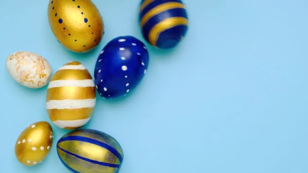 Easter eggs are rolling, knocking each other on blue table. Eggs trendy colored classic blue, white and golden . Happy Easter. Minimal style. Top view