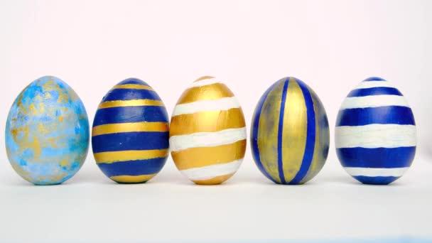 A húsvéti tojások gurulnak, egymást koppintják a fehér asztalon. Tojás trendi színű klasszikus kék, fehér és arany. Boldog Húsvétot! Minimális stílus.