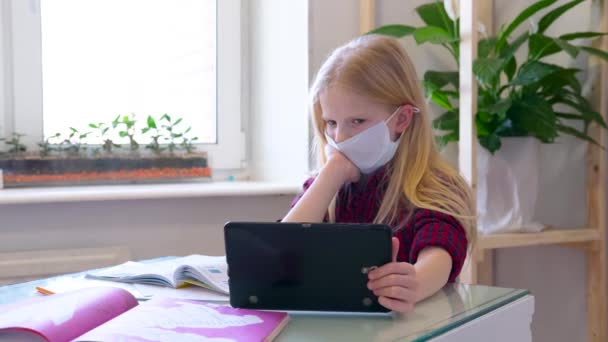 Distance learning online education. Sickness schoolgirl in medical mask studying at home with digital tablet in hand and doing school homework. Training books and notebooks on table.