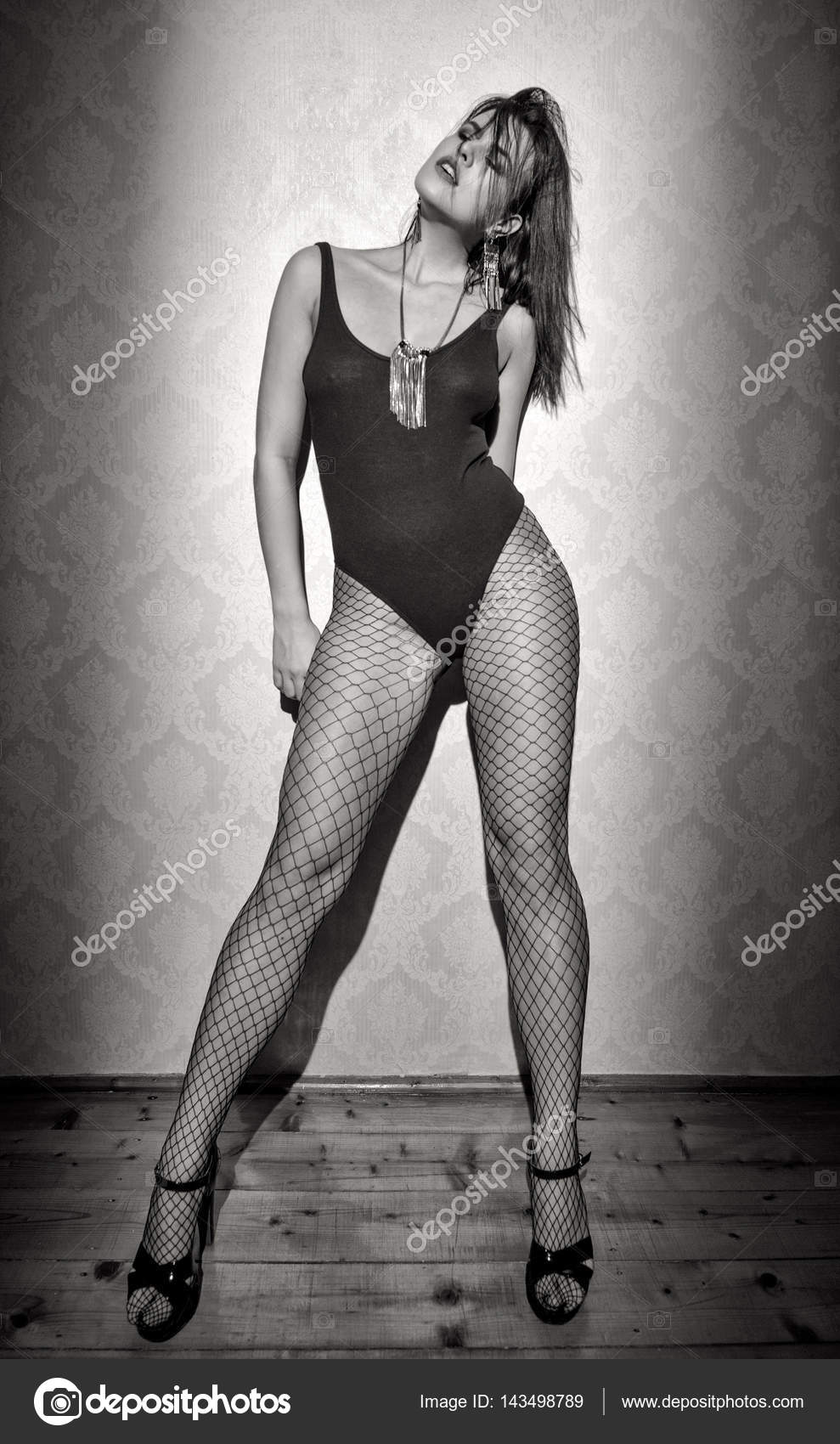Sensual sexy woman posing at vintage wall black and white photo by