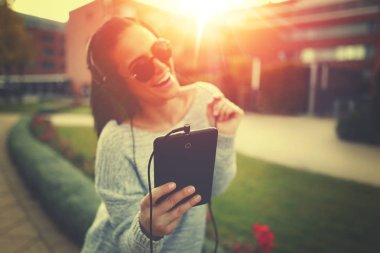 Young woman listening music by tablet and headphones in sunset o