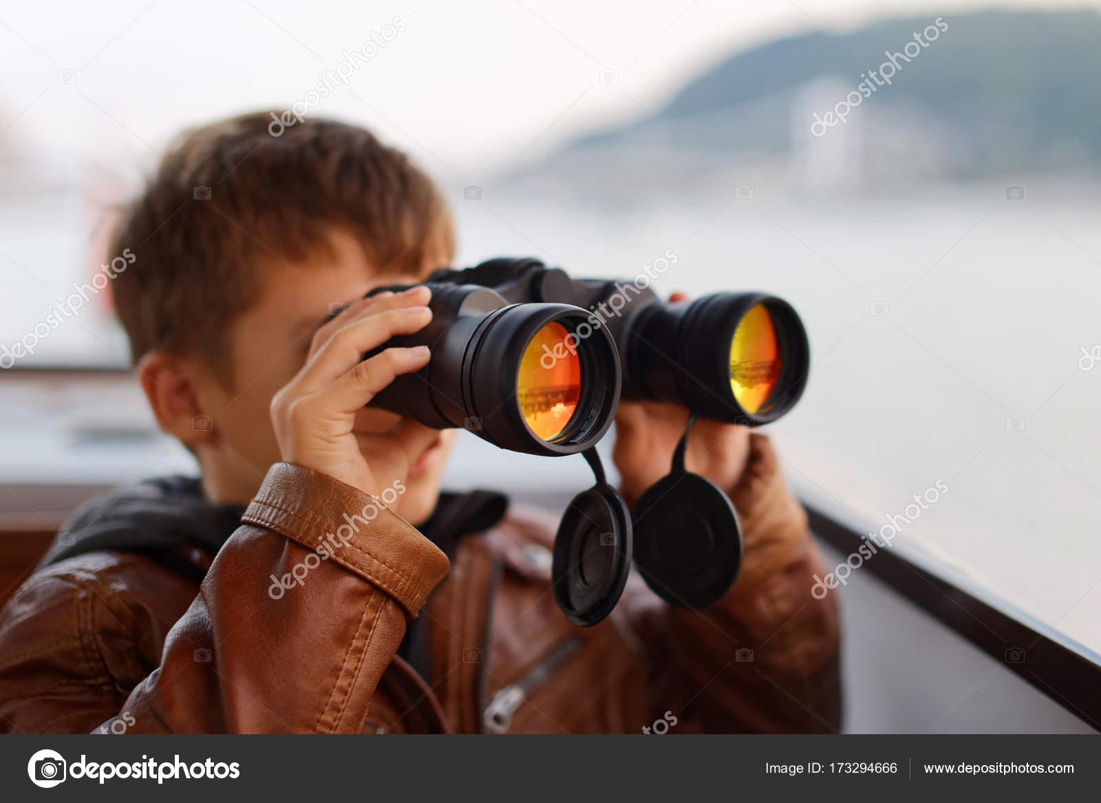 Kleiner junge gerade durch fernglas während der reise u stockfoto