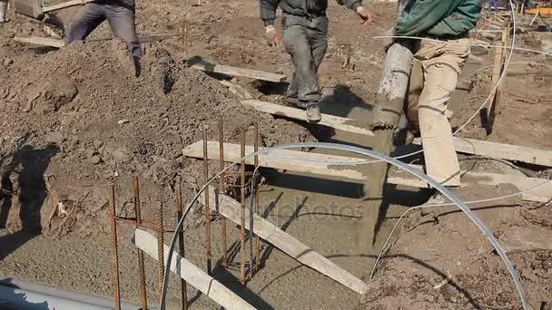 Krakorců, zaměstnanci drží čerpadlo hadice k nalití čerstvého betonu do budovy nadace