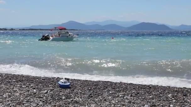 Malé molo lodí kotví blízko pláže s pěnitou vlny