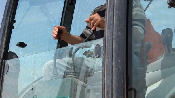 Worker is managing excavator, he controls machine with operating joystick. Operators hands operating on an excavators handles to control vehicle, heavy equipment operator.