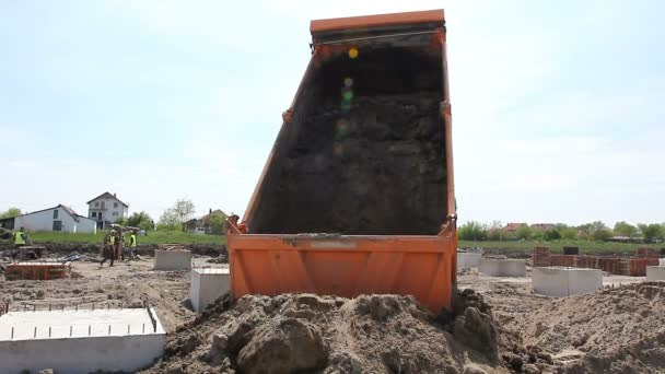 Dumper truck is unload soil.Dumper truck is unloading sand in excavator range at construction site.