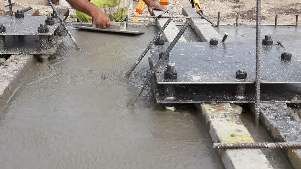 Munkavállaló szintezés konkrét kiöntés után. Mason használja a simítóval el befejezni tetején a beton Alapítvány.