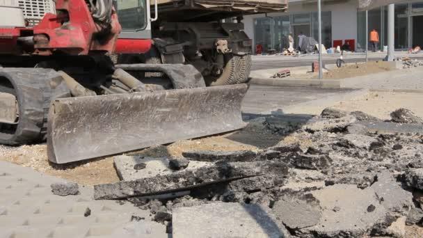 Malé earthmover s nakládacím odstraňuje rozbitý asfalt, zblízka. Malé rypadlo odstraní rozbitý asfalt a štěrk na staveništi.
