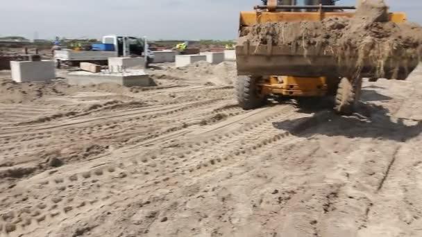 Zrenjanin, Vojvodina, Serbia - April 30, 2015: Dump truck is unloading soil. Excavator is transport sand with front bucket for transport over building site.