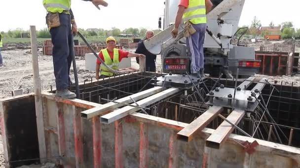 Zrenjanin, Vojvodina, Serbia - April 30, 2015: Workers at building site are pouring concrete in mold from mixer truck.