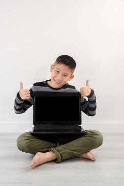 Asian boy showing blank laptop at home.