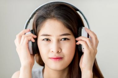 Happy Asian woman using headphone at home.