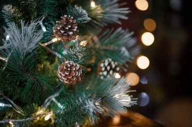 Elements of Christmas decorations at home close-up. Christmas interior lights garlands, wooden toys, gifts under the tree