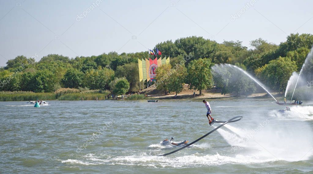 The athlete flies with a water jet from the side of a water mot