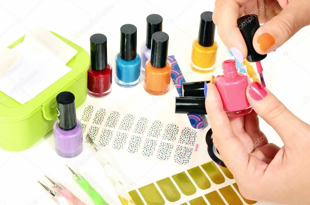 Woman hands doing rainbow manicure.Table full of manicure ustensils ...