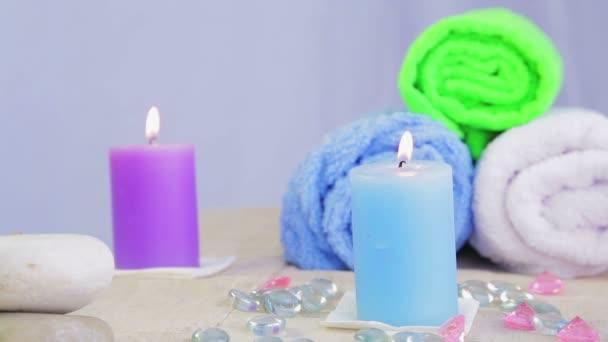 Stůl v lázeňském salonu se svíčkami, ručníky a kameny pro terapii