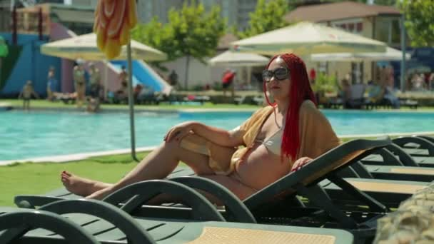 A woman with red hair sunbathes on a sun lounger by the pool