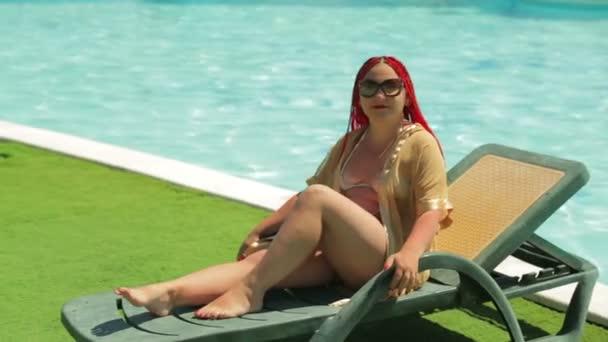 Egy fiatal barna nő napozhatsz a nyugágyon a medence mellett.