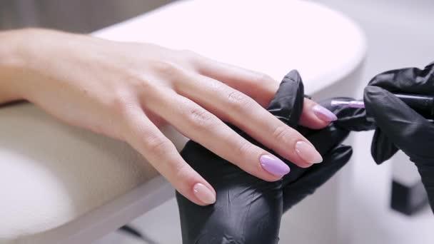 Žena manikérka v salonu krásy aplikuje fialový gel leštidlo na nehty klienta