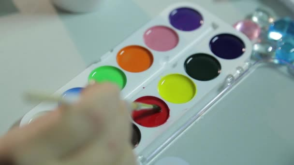 Womans hands make home decorations for Christmas by painting white blanks with watercolors.