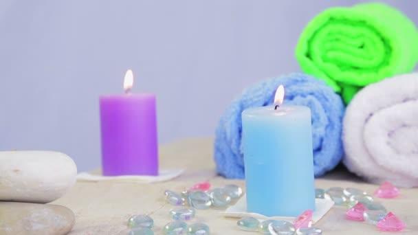 Stůl v lázeňském salonu se svíčkami, ručníky a kameny pro léčbu a relaxaci.