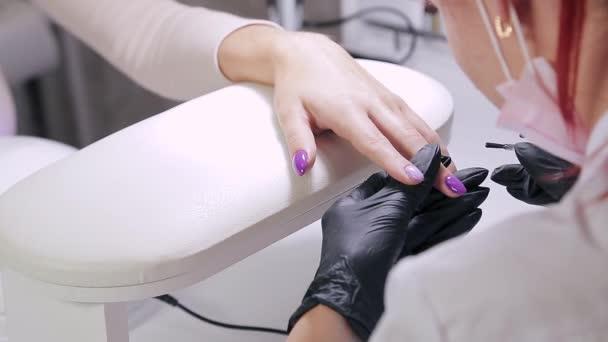 Žena manikérka v salonu krásy nanáší matnou vrstvu na gel leštidlo