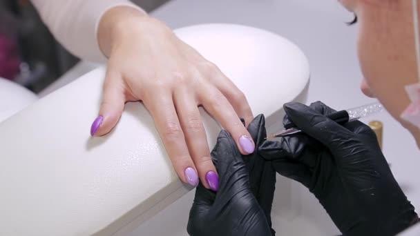 Manikérka v salonu krásy zdobí klientky hřebíky gelovým lakem s broušenými kameny
