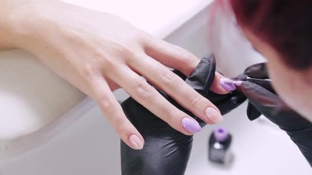 Žena manikérka v salonu krásy aplikuje fialový gel leštidlo na nehty klienta.