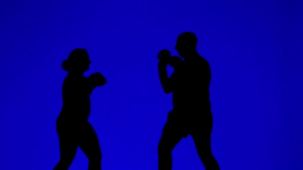 Silhouettes of man and woman in boxing gloves during a combat training.