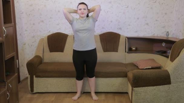 Mladá žena v obývacím pokoji provádí sedací cvičení.