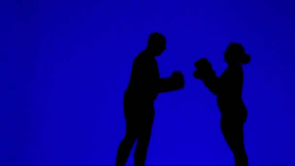Silhouettes of man and woman in boxing gloves during a workout