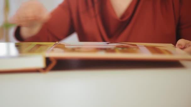 A női kezek átadnak egy albumot családi fotókkal. Homály