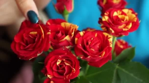A woman holding a bouquet of red and yellow roses finger holds on buds