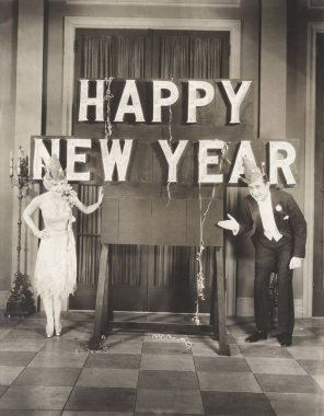couple presenting New Year sign