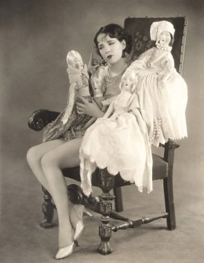 Woman gesturing to dolls