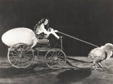 chick pulling cart with woman