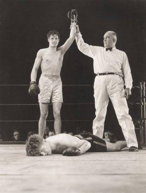 Referee raising hand of winning boxer